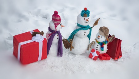Christmas holidays discounts and winter sale. Greeting snowman. Winter snowman family. Mother snow-woman, father snow-man and kid wishes merry Christmas and Happy New Year.