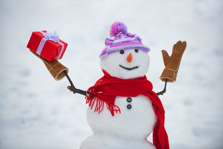 Snowman in a scarf and hat. Cute snowmen standing in winter Christmas landscape. Funny snowman in stylish hat and scarf on snowy field. Greeting snowman.