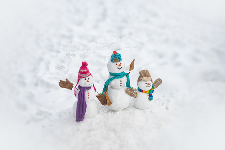 Happy winter snowman family. Mother snow-woman, father snow-man and kid wishes merry Christmas and Happy New Year. Merry Christmas and happy New Year greeting card with copy-space. Stock Photo