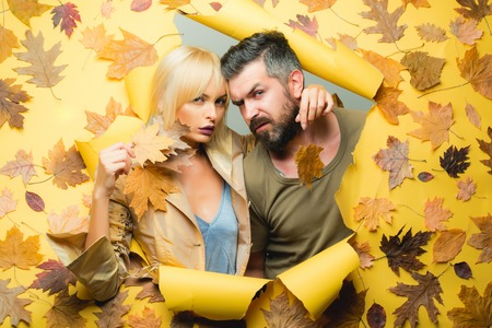 Couple in Love wearing in fashionable seasonal clothes having Autumnal mood. Autumn couple in autumn clothes and looks very sensually. Bearded man and pretty woman on yellow background for Copy space.
