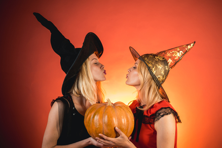 Two emotional young women in halloween costumes on party over orange background with pumpkin. Two beautiful women in carnival sexy costumes of witches. Isolated image. Halloween copy space. Imagens - 123119345