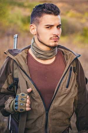 Hunter with shotgun gun on hunt. Portrait of hamdsome Hunter.