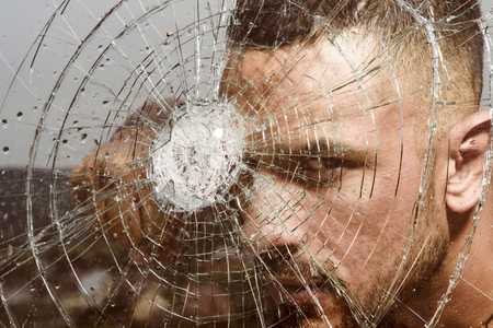 Those who live in glass houses should not throw stones. Strong man knocking down a glass wall with fist. Handsome latino man looking through broken glass. Confident hispanic guy breaking glass wall