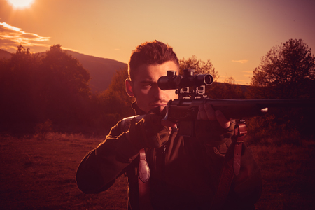 American hunting rifles. Hunting without borders. Rifle Hunter Silhouetted in Beautiful Sunset. Calibers of hunting rifles. Track down.