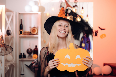 Halloween dresses and witch costumes design. Pretty young blonde woman dressed as a fairy with pumpkin. Charming halloween witch with broom over vintage background.