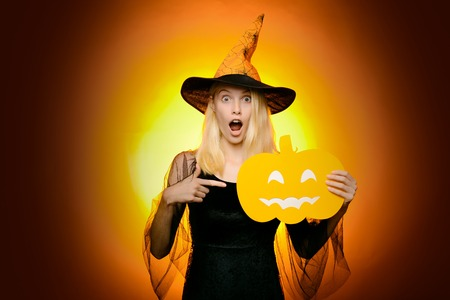Beautiful young surprised woman in witches hat and costume pointing hand - showing products. Halloween Woman portrait. Surprised woman in witches hat and costume on red Halloween background. Imagens - 123122014