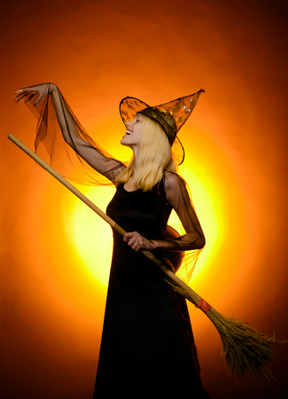 Charming halloween witch with broom over vintage background. Vampire Halloween Woman portrait. Halloween Witch in black hat. Funny expression. Happy people. Having fun. Imagens - 123122018