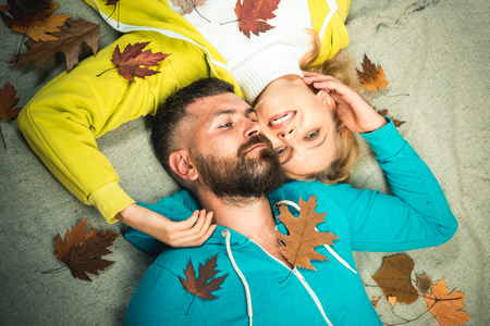 Autumn couple wearing in autumn clothes and looks very sensually. Happy people. Beautiful tender couple advertise your product and services. Funny couple are getting ready for autumn sale.