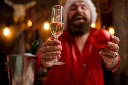 Alcohol drink. Brutal santa claus. Man bearded hipster santa with red hat celebrate with champagne drink. Christmas holiday. Lonely on christmas eve. Happy new year. Manly brutal santa leather jacket