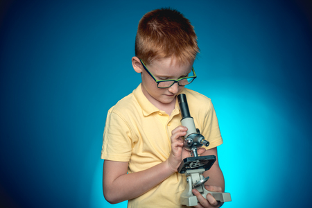 Child looking in a microscope. Smart kid concept. Wunderkind concept. School. Preschool. Fashion. Education. Funny little boy in glasses. Interesting sample. Smart kid concept. Wunderkind concept.