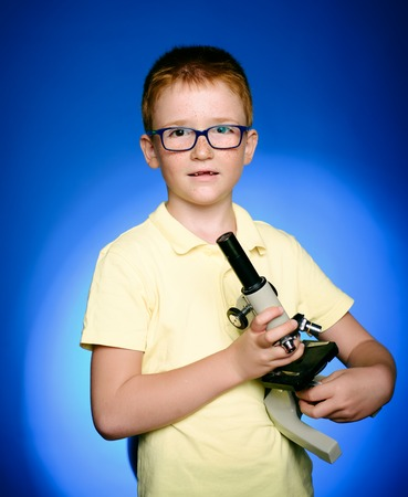 Surprised smart boy in big glasses staring at the camera. Child looking in a microscope. Child, pupil on calm face near microscope. Child on busy face near microscope.