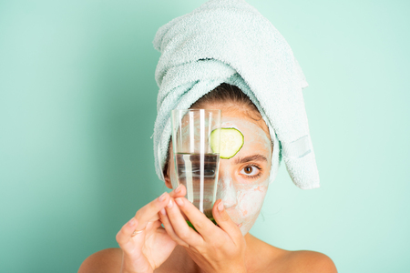 Stay hydrated. Girl chilling making clay facial mask with cucumber. Skin health. Woman adorable smiling girl with clay mask. Cleaning and care for young skin. Proper approach to clean skin