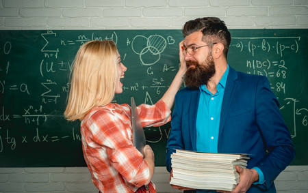 Teacher helping young student with lesson. Nerd funny student preparing for university exams. Concept of education and teaching. Studying at university. Standard-Bild