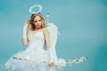 Enjoying magic moment. Pretty white little girl as the cupid with a bow and arrow congratulating on St Valentines day. Cherub girl Stock Photo
