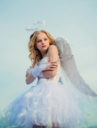 Niño con carácter angelical. Niña ángel contra el cielo soleado. Un niño con la ropa de un ángel en el fondo del cielo - concepto de San Valentín. El Dios del amor.