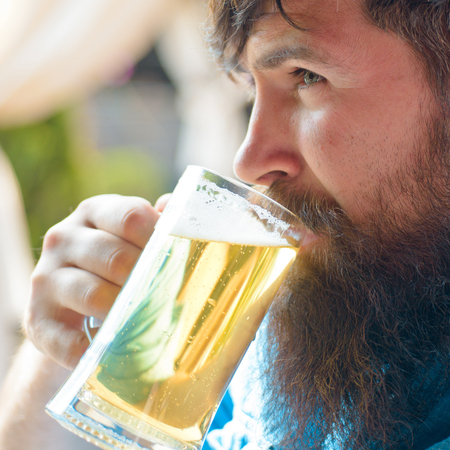 Guy at the bar counter. Close up portrait of Man with beer. Beer. Brutal hipster bearded man sit at bar counter. Bearded man with a glass of beer.
