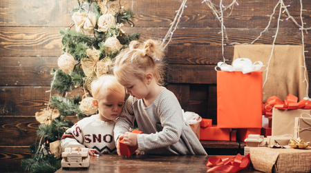 Cute little child girl is decorating the Christmas tree indoors. The morning before Xmas. Kid enjoy the holiday. Cheerful cute child opening a Christmas present.
