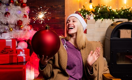 Christmas woman hold bomb. Creative boom. Bomb emotions. Expressions face. New year presents. Cheerful young woman wearing Christmas costume over wooden wall. Woman smile Christmas. Home Holiday.