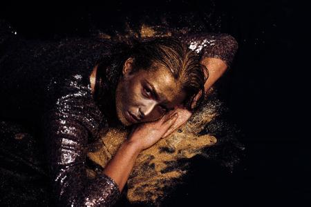 Goldene Maske. Luxus-Schönheitsverfahren. Reines Gold. Goldene Dame, die sich entspannt. Vogue- und Glamour-Konzept. Hübsches Gesicht der attraktiven Frau mit metallisierter Farbe der Make-up- und Körperkunst - Goldkonzept. Goldene Haut.