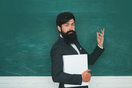 Professor in class on blackboard background. Chalkboard copy space. Teachers day.