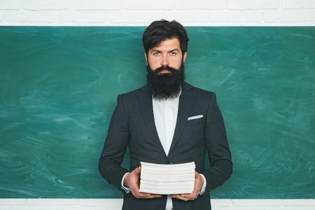Preparing for exam in college. Teacher preparing for university exams. Good teachers enjoy teaching. Young teacher near chalkboard in school classroom. Stock Photo