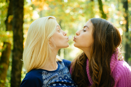 Friendly kiss. Glad to see you. Girls friends kissing. Girlish friendship concept. Blonde and brunette walking in autumn park defocused background. Women kiss cute faces close up. Come on kiss me