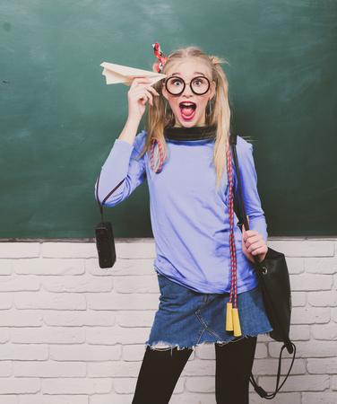 Cute nerd funky style. Enjoying her school life. Fancy schoolgirl. School fashion. Carefree teenager. Fashionable blonde girl chalkboard background. Back to school. Stylish school pupil modern girl
