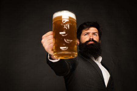 Handsome bearded man drinking beer. Portrait of handsome young man tasting a draft beer. Man holding mug of beer. Man holds glass of beer. Stock Photo