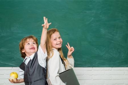Kids gets ready for school. Couple of little girl and boy in classroom. Schoolgirl helping pupils studying at desks in classroom. Happy school kids. Apple and books - school concept. Stock fotó