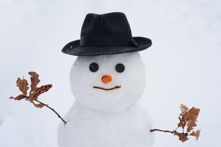 Handgemachter Schneemann im Schnee im Freien. Weihnachtsschneemann auf weißem Schneehintergrund. Winterferien-Verkaufsbanner. Winter-Kunst-Grußkarte. Standard-Bild