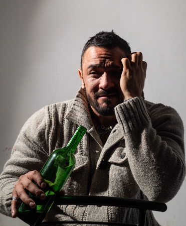 He is a recovering alcoholic. Depressed latino man drinking alcoholic drink from bottle. Anonymous alcoholic having drinking problem. Alcoholic personal degradation Banco de Imagens