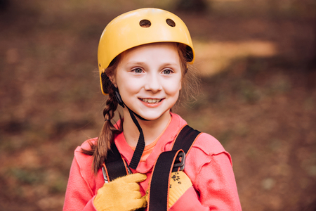 Little child climbing in adventure activity park with helmet and safety equipment. Happy child climbing in the trees. Cute child boy. Happy child boy calling while climbing high tree and ropes.