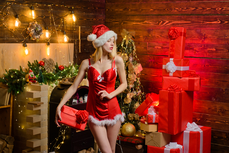 Sexy erotic girl celebrate new year and merry christmas. Red lingerie for christmas. Sexy lingerie christmas celebration. Love peace and joy for whole year. Girl santa hat at home near christmas tree