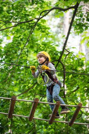 Go Ape Adventure. Climber child on training. Child climbing on high rope park. Children fun. Cargo net climbing and hanging log. Active children. Roping park
