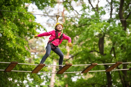 Artworks depict games at eco resort which includes flying fox or spider net. Children summer activities. Happy Little child climbing a tree. Stock Photo
