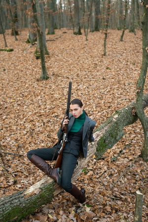 erfolgreiche Jagd. Jagdsport. Jägerin im Wald. Frau mit Waffe. Zielschuss. Mädchen mit Gewehr. jagen jagen. Waffenladen. militärische Mode. Errungenschaften von Zielen. Jagd Natur Umgebung