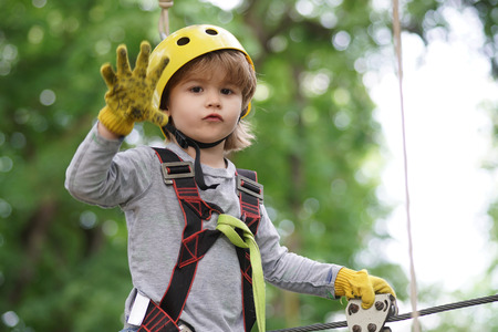Go Ape Adventure. Hiking in the rope park girl in safety equipment. Little child climbing in adventure activity park with helmet and safety equipment.