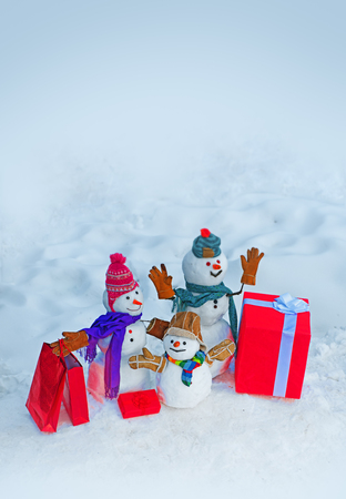 Delivery gifts and gift emotions. Family of happy snowman. Snowman is standing in winter hat and scarf with red nose. Snowman with a bag of gifts.