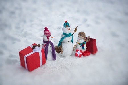 Handmade snowman in the snow outdoor. Greeting snowman. Winter snowman family. Mother snow-woman, father snow-man and kid on Christmas background.