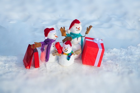 Happy snowman with gift boxes standing in winter Christmas landscape. Winter holidays sale banner. Cute snowman in hat and scarf on snowy field. Christmas sale discounts. Standard-Bild - 123088323