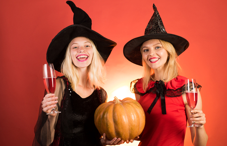 Two beautiful women in carnival sexy costumes of witches. Isolated image. Two happy young women in black and red dresses, costumes witches halloween on party over orange background. Imagens