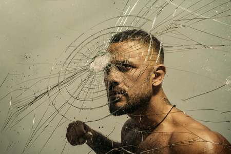 Determination to succeed. Muscular man having inner determination and commitment to break glass wall. Determined latino man removing obstacle with determination and confidence. Determination concept