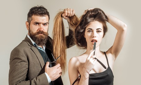 Brutal guy in modern Barber Shop. Hair Preparation is just for the dashing chap. Hair Studios. Beauty woman getting haircut by hairdresser at barbershop hairstudios.