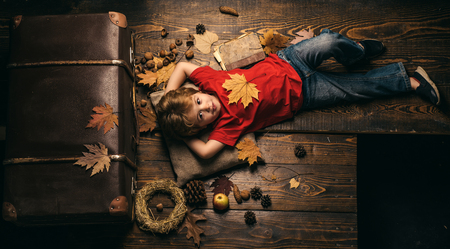 The biggest discounts for all autumn clothes for children. Kid lies laying his hands behind head and resting on wooden floor in golden leaves. Kid playing in autumn.