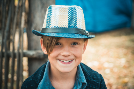 Last days of warm weather must be seen off with a smile on his face. Kid on an autumn holiday in the farm. The boy advertises destkuyu clothes for autumn. Stok Fotoğraf