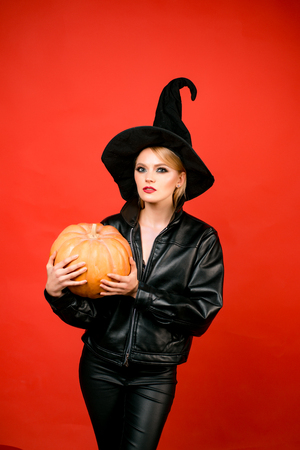 Young women in black witch halloween costumes on party over red background. Witch posing with Pumpkin.