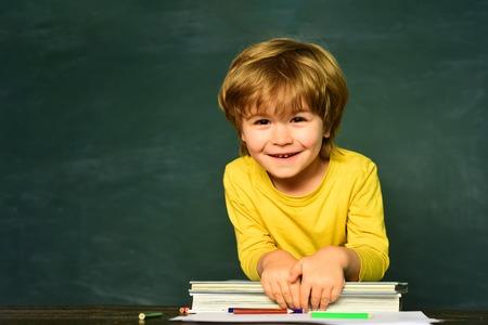 Elementary school. Happy mood smiling broadly in school. First school day. Kid is learning in class on background of blackboard