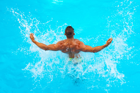 Powerful muscular male figure on blue beach background. Beautiful young man relaxing on beach. Young man Swimming Pool Concept. Health body.
