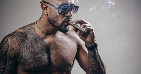 Brutal sportsman torso. Sport and fitness. Confidence and charisma. Sexy abs of tattoo man. Muscular macho man with athletic body. Vape