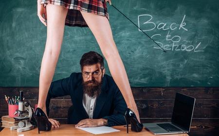Neugieriger Lernender. Sex-Rollenspiel. Mann bärtiger Lehrer und weibliche Minirockbeine. Erotisches Unterrichtskonzept. Untergeben und Unterwerfung. Begehrter Student. Aufklärungsunterricht. Sexy Mädchen halten Peitsche Standard-Bild